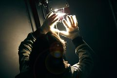 Man manipulating spot light with gloves in production studio stock image