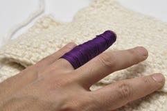 Man& x27; mano de s e hilado p?rpura aislados en un fondo blanco crochet Copie el espacio imagen de archivo