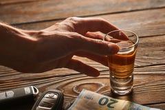 Man& x27; mano de s que alcanza al vidrio con la bebida del alcohol y la llave del coche Concepto de la bebida y de la impulsión foto de archivo
