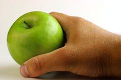 Man& x27; mano di s che tiene mela verde su fondo bianco Fotografia Stock