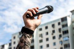 Man& x27; mano di s con un microfono Fotografie Stock Libere da Diritti