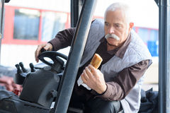 Man manoeuvering fork lift truck while holding sandwich Royalty Free Stock Photography