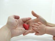 Man& x27; manos de s y de la mujer con el corazón rojo Imagenes de archivo