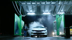 Man on manual car wash at night Stock Photos