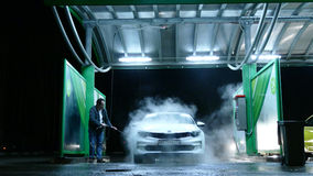 Man on manual car wash at night Royalty Free Stock Photo
