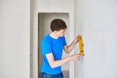 Man with manual level. Man in t-shirt checks wall level Royalty Free Stock Photography