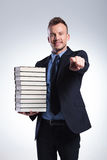 Man with many books points at you Royalty Free Stock Images