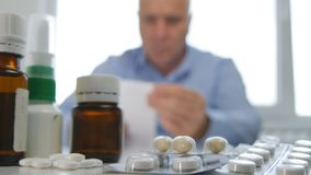 Man With Many Pills on the Table Looking to a Medical Prescription royalty free stock photo