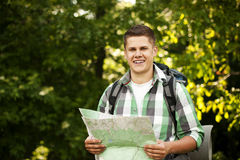 Man with map. Hiking collection: man holding a map in forest Stock Photography