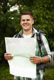 Man with map. Man holding a map in forest Royalty Free Stock Images