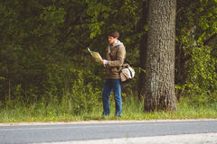 Man with map and bag in hand walking on a roadside. Hitchhiking concept Stock Images