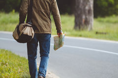 Man with map and bag in hand walking on a roadside. Hitchhiking concept Royalty Free Stock Photo