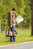 Man with map and bag in hand walking on a roadside. Hitchhiking concept Stock Photography