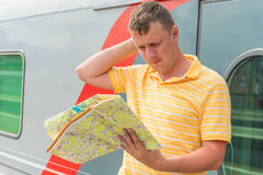 Man with a map costs about the train at the station. The man with a map costs about the train at the station Stock Photos