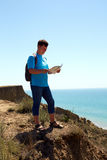 Man with map exploring wilderness on trekking adventure Stock Image