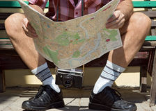 Man with map. Legs of tourist sitting on a bench and looking for a place on the map Stock Images