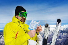 Man with map of ski pistes over the mountain peaks royalty free stock photos