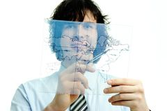 Man with map of the world. A young man with a map of the world printed on a transparent material stock image