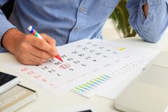 Man marked Friday 13th on the calendar. Man and Friday13th circled in the planner, office background Stock Photo