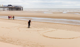 Man marking on sand `I love you`. Blackpool, England - September 12, 2016: Man marking on sand `I love you` with beach ride donkeys and pier in the background Royalty Free Stock Image