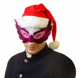 Man in mask 5. A man in mask and xmas hat on his head; over white background royalty free stock photography