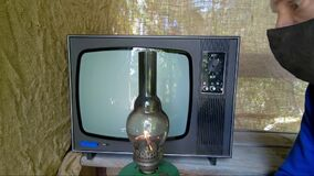 Man in mask against the virus, an old TV and an antique lamp