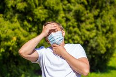 A man in a mask from allergy, in a white T-shirt, stands in the park royalty free stock photography