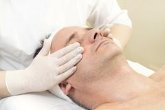 Man in the mask cosmetic procedure Stock Image