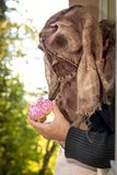 Man with the mask of a creepy scarecrow. Looking through a window, eating a heart cake royalty free stock photography