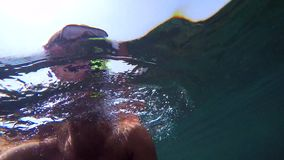 A man in a mask for diving under the water. A man in a mask for diving, pointing the camera at himself under the water stock footage