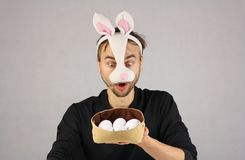 Man in the mask Easter rabbit surprised looking at the eggs in h. At, open mouth Royalty Free Stock Photo