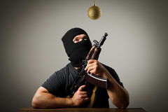 Man in mask with gun and Christmas toy Royalty Free Stock Photos
