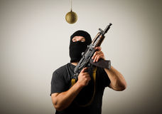 Man in mask with gun and Christmas toy Royalty Free Stock Images