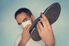 Man with mask is holding dirty stinky shoe - unpleasant smell concept. Dirty smelly sneakers. Man with mask is holding dirty stinky shoe - unpleasant smell royalty free stock photos