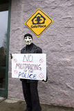 Man in mask holds protest sign. Spokane, Washington USA - December 20, 2014. A protestor in a Guy Fawkes mask displays a sign at a rally in Spokane Valley Royalty Free Stock Image