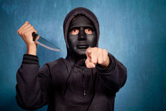 Man with mask and knife. Man with black scary mask and big knife point with finger Royalty Free Stock Photos