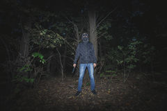 Man with mask and knife in the wood Royalty Free Stock Image