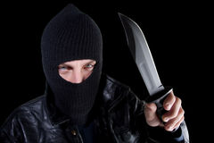 Man in mask with large knife on black. Young man in black with large knife stock image