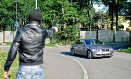 Man in mask pointing gun toward car. Stock Images