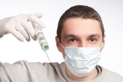 Man in mask pointing with money syringe Royalty Free Stock Images