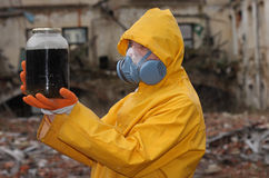 Man with  mask and protective clothes explores danger jar                r Royalty Free Stock Images