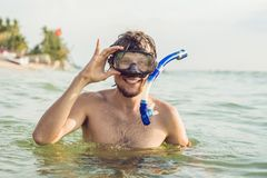 A man with a mask and snorkel is going to dive into the sea.  royalty free stock photos