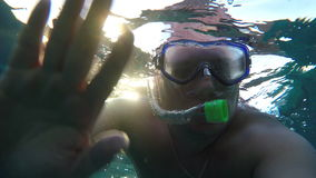 A man in a mask and a snorkel underwater waves a hand stock footage