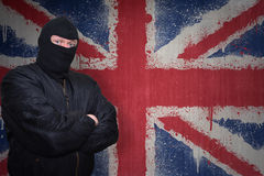 Man in a mask standing near a wall with painted national flag of great britain Royalty Free Stock Photos