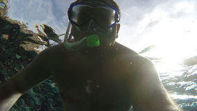 The man in the mask under the water waving at the camera.  stock video