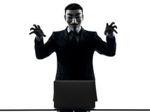 Man masked anonymous group member computing computer menacing si Stock Photography