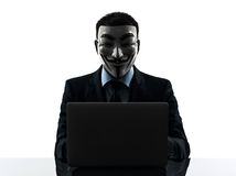 Man masked anonymous group member computing computer silhouette. PARIS– OCTOBER 30 : one man dressed and masked as a member of Anonymous underground group Royalty Free Stock Images