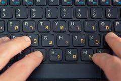 Man maskinskrivning på ett tangentbord med bokstäver i hebréiskt och engelskt Arkivfoton