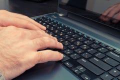 Man maskinskrivning på ett tangentbord med bokstäver i hebréiskt och engelskt Royaltyfria Bilder