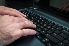 Man maskinskrivning på ett tangentbord med bokstäver i hebréiskt och engelskt Royaltyfri Bild